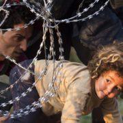 profughi attraversano una frontiera